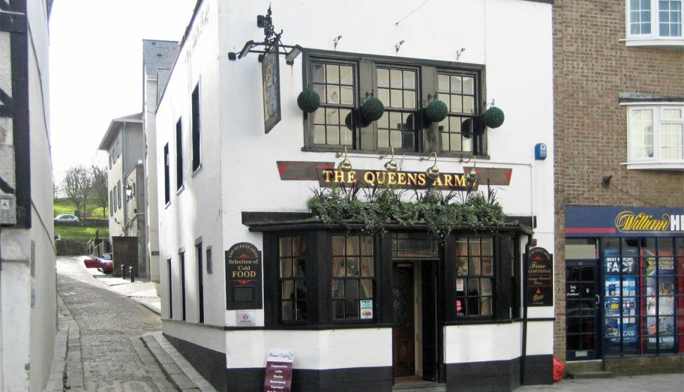 The white and black painted front of the Queens Arms with plant displays above the entrance.