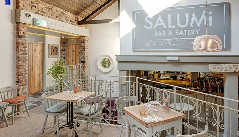 Inside Salumi, showing cream painted walls, tables and chairs, exposed brickwork and cream wrought iron railings separating seating areas.