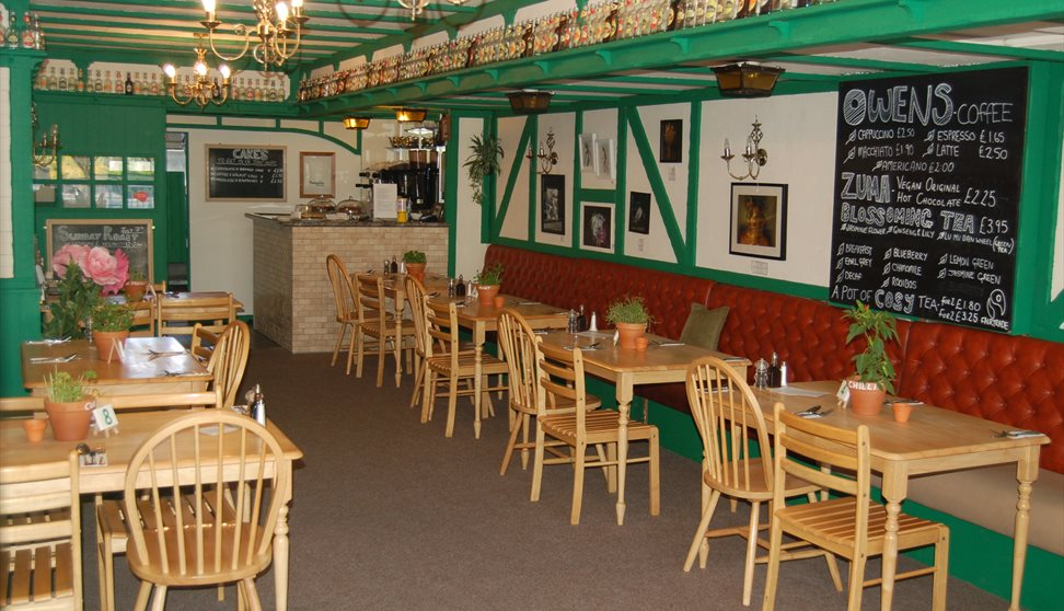 The restaurant interior painted green with wooden tables and chairs and a large menu chalkboard.