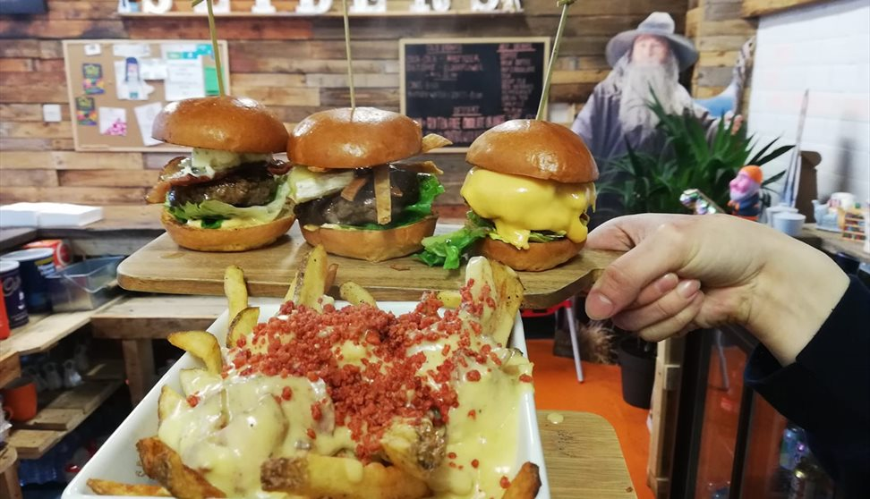 A board with 3 different sliders and a large white dish containing chips loaded with cheese and crumbled bacon.