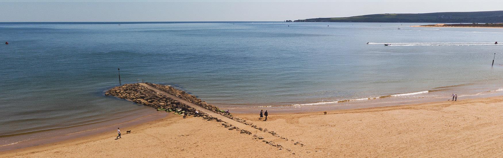 Beautiful sandy beach with a beach groyne extending into the blue sea.