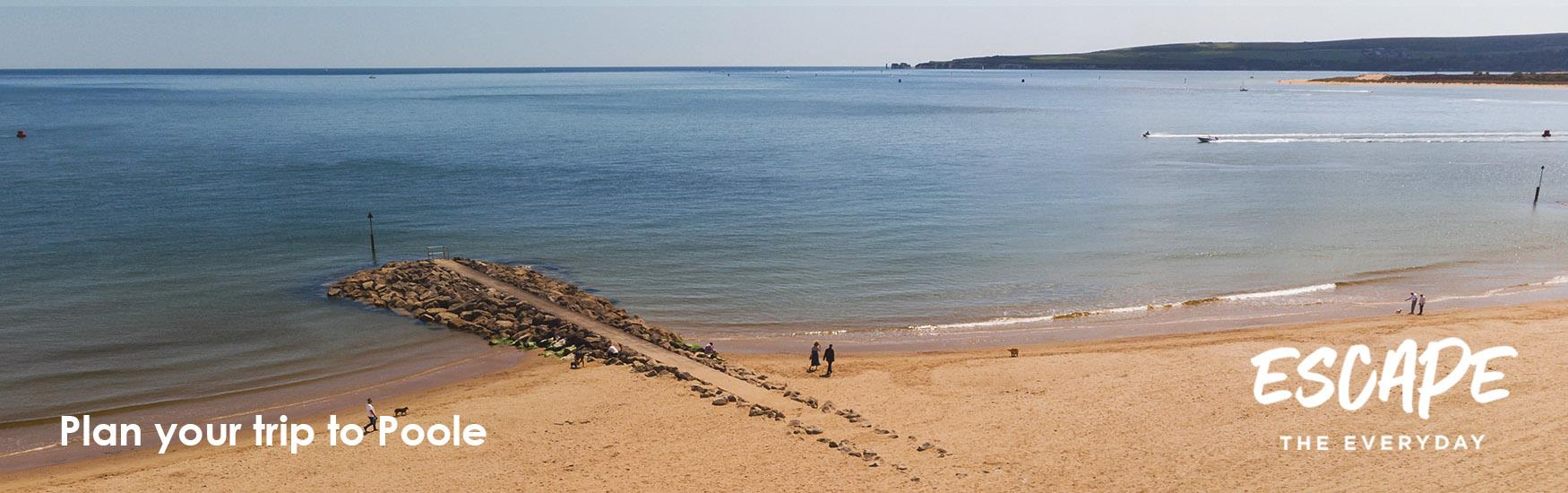 Visitors enjoying an autumn walk along one of Pooles beautiful beaches with a logo overlay that reads Escape the Everyday