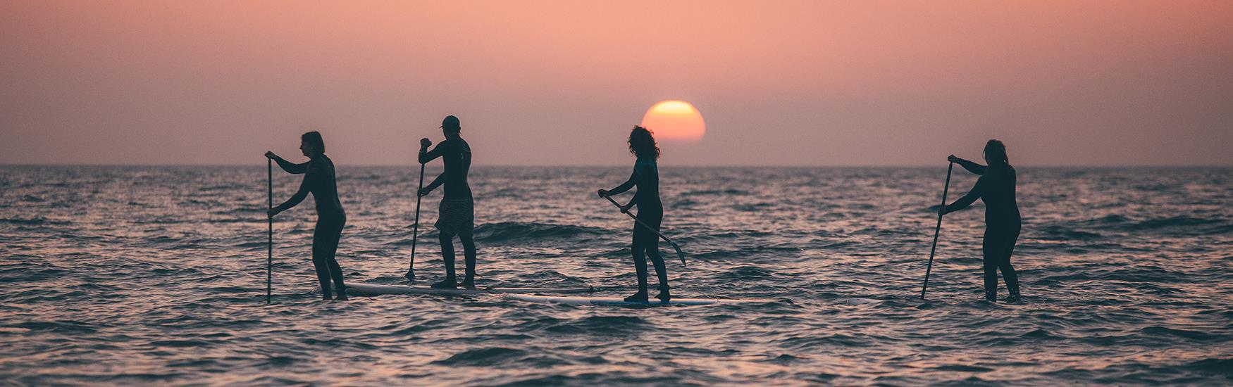 Paddle boarders at Sunset in Poole Harbour.