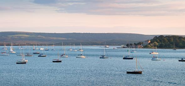 immense views of brownsea island with boats moored in Poole harbour