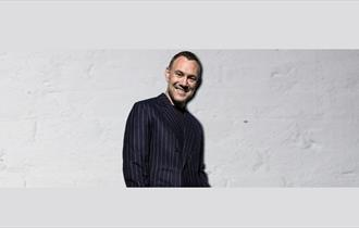 David Gray smiling on a white brick background