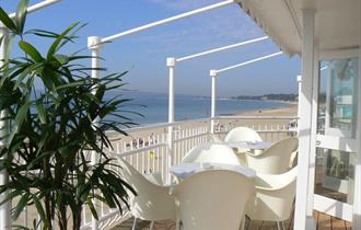 White table and chairs on the balcony overlooking the stunning views of Bournemouth beach and coastline