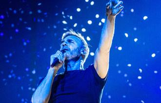 Gary barlow points to the sky while singing infront of a blue background