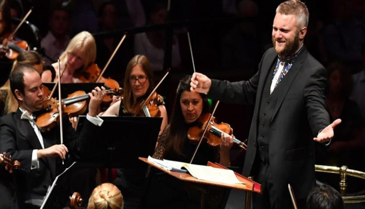 A conductor stood smiling at his orchestra with open arms as they play.