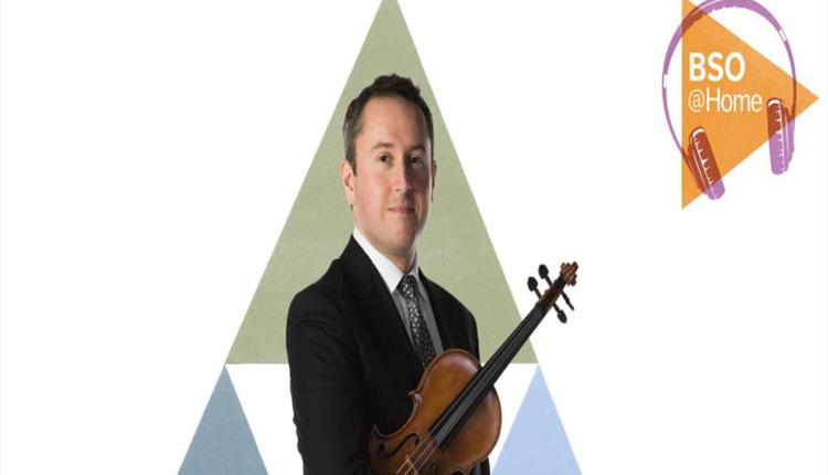 Man standing in front of a green triangle with a violin under his arm.