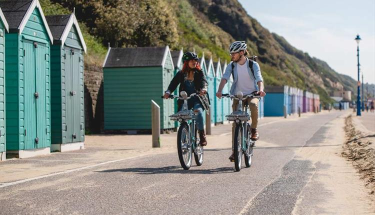 Couple cycling along Bournemouth seafront with beach huts behind them