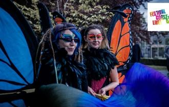 two ladies dressed up as giant butterflies