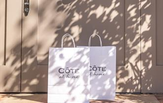 Cote bags with Cote at Home written on them outside front door