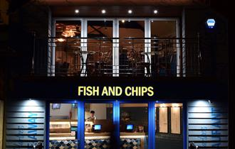 Harlees chip shop illuminated at night