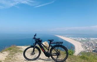 Electronic bike on a cliff overlooking the sea and beach