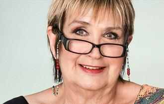 Portrait photo of Jenni Murray in Conversation looking directly at camera and smiling, wearing glasses.