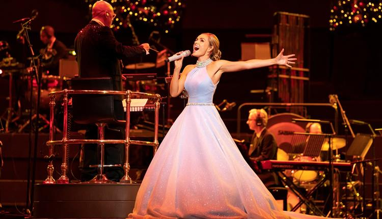 Lady in big white dress singing with an orchestra