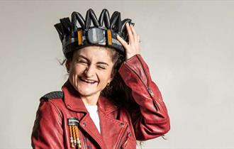 A woman with a red leather jacket and white top on, holding a crown on top of her head whilst giggling.