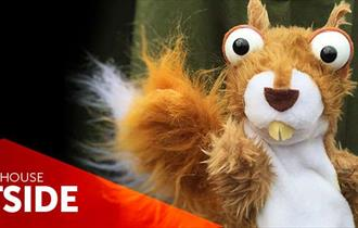 Cheeky toy squirrel with big eyes and big teeth, red triangle overlaid with the words LIGHTHOUSE OUTSIDE