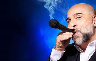 A dark blue back ground. A man holding a microphone to his mouth, as if it were a cigar, with smoke coming out.