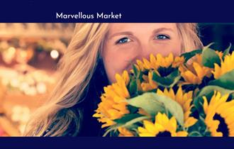 Woman smiling with sunflowers in her hands and food market in the background