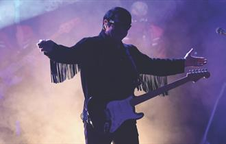 Silhouette of a man in purple and cream coloured smoke holding a guitar