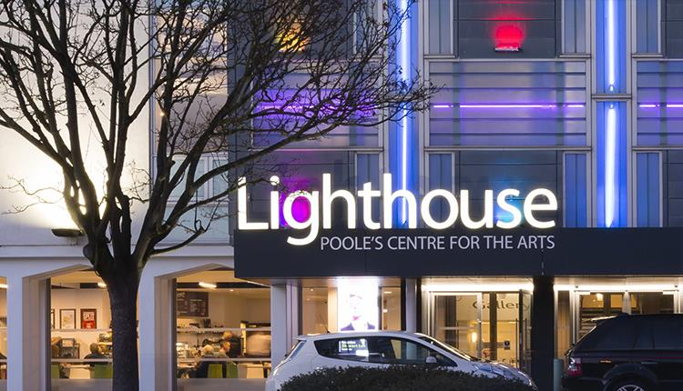 The lighthouse building and logo illuminating the night sky in Poole