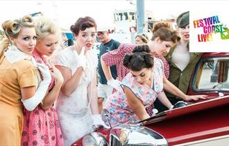 Ladies in vintage clothing standing around vintage car