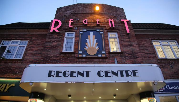 Front of the Regent Centre Building lit up at night time