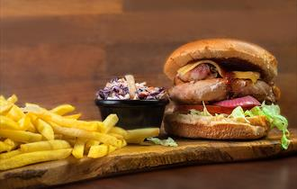 Beefburger, fries and coleslaw on a board