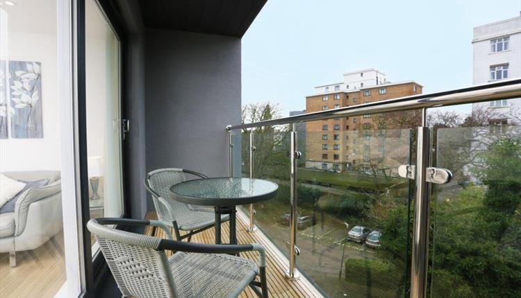 Two chairs and a table on a modern glass balcony overlooking the town centre