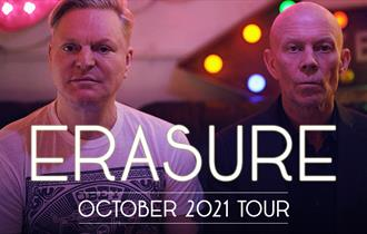 two members of the pop band Erasure looking towards camera with serious expressions and posing wearing tshirts