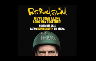 Fatboy Slim wearing hard army helmet with dark background and only half of his face showing, looking at camera