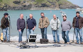 Fisherman's Friends standing and singing against a background of a fishing port, port isaac, sunny blue skies and water, gulls and boats sat on the wa