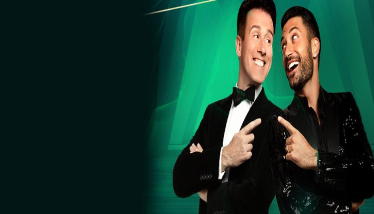 Anton Du Beke and Giovanni stand back to back smiling and pointing at each other. Green background.
