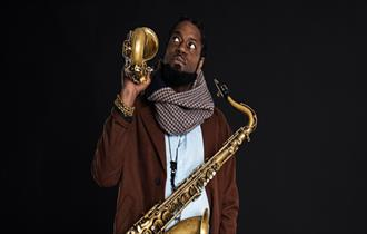 Musician standing looking upwards with a saxophone hanging from his neck and another resting on his shoulder.