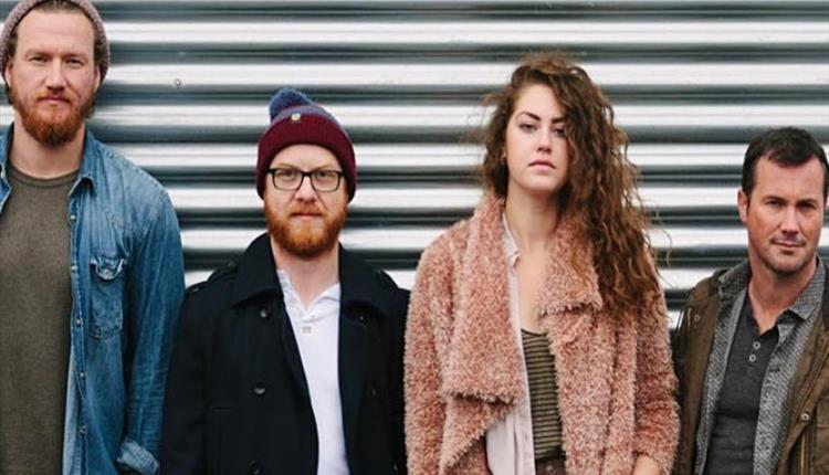 The four band members stand in front of a metal garage door, staring directly into the camera.