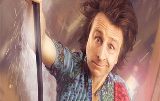 Milton Jones looking at camera with dishevelled hair and funny expression