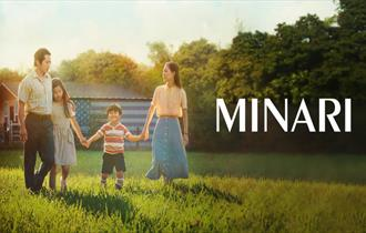 Two parents and two young children hold hands as they walk through a sun soaked field.
