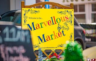The words 'Marvellous Market' on a bright yellow sign