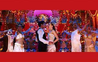 Brightly dressed performers sign on stage. Man and woman in the centre stand facing each other with arms around each other's waists.