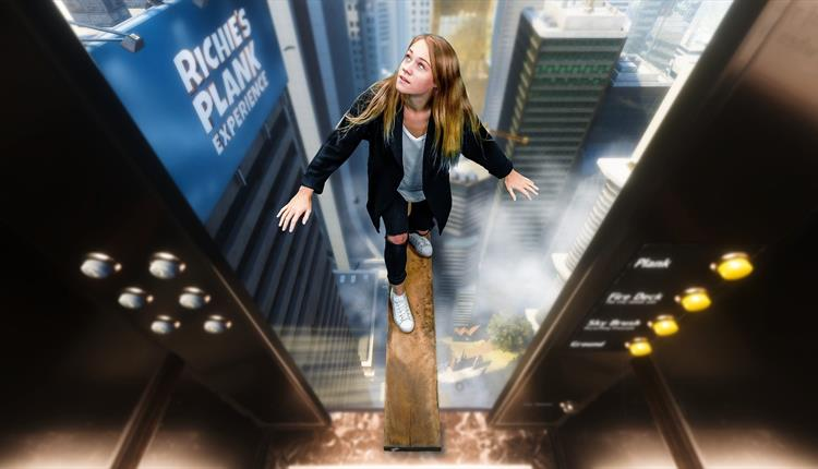 Girl  on a plank out from an elevator.