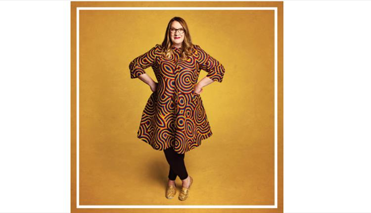Sarah Millican standing with hands on hips smiling at camera wearing gold & brown dress