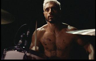 Topless man sits at drums with drumsticks in his hands.