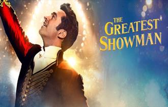 Blue and gold glittery background. Showman in red coat points up to the sky. Gold lettering