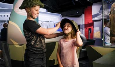 Children trying on helmets at the D-Day Story