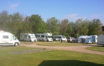 Touring caravans and motorhomes lined up at Kingfisher Caravan Park