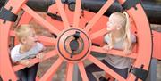 A young boy and girl play inside a large wheel at Fort Nelson