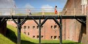 A young family walk across the bridge out of Fort Nelson