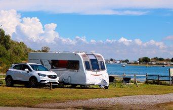 Caravan pitch overlooking the water at Fishery Creek Park
