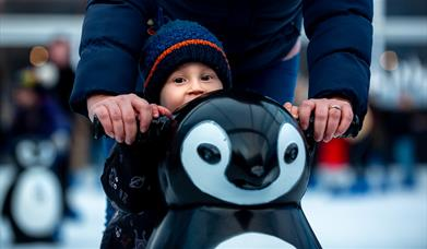 Child with a penguin-shaped skate aid at Ice Skate Portsmouth - credit Ice Skate Portsmouth and Vernon Nash